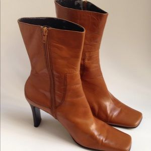 Women's brown leather high-heeled boots.